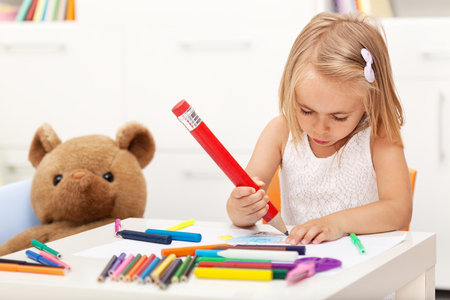 Little girl drawing with a large pencil - sitting at the table with her toy bear Zdjęcie Seryjne