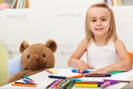 Little girl drawing with her toy bear keeping company - sitting at the table at home