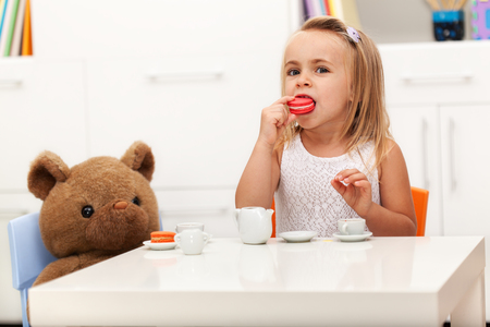 Little girl having a tea party with her toy bear - eating a cookie Zdjęcie Seryjne