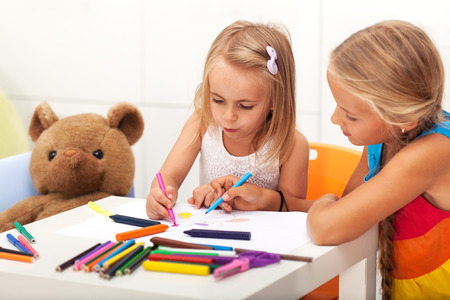 Girls drawing together - older sister helping the little one to draw her toy bear