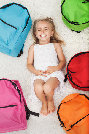 Happy preschool girl lying among colorful school bags - with a broad grin on her face