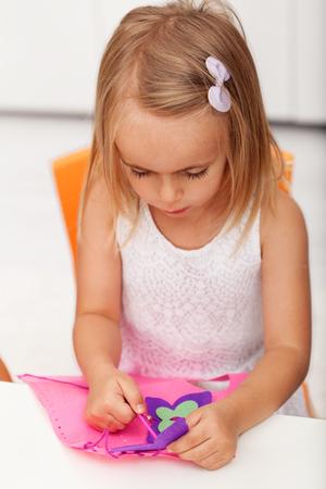 Little preschool girl doing some needlework on a crafting project, closeup, shallow depth Zdjęcie Seryjne