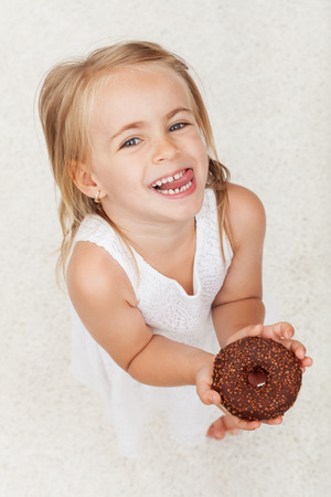 Happy little girl holding a chocolate covered doughnut - looking up with a broad smile and mischievous eyes