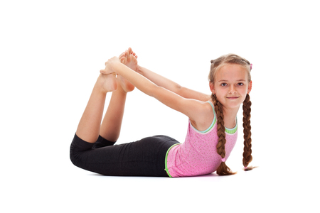 Young girl smiling and doing gymnastic exercises - stretching her back, isolated