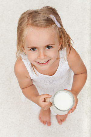 Little happy girl holding a cup of milk with a large smile - top view