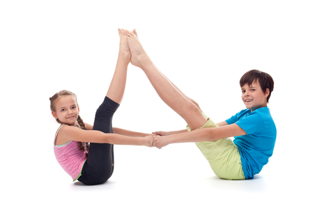 Kids balancing together sitting on the floor propping their legs together and holding hands, isolated
