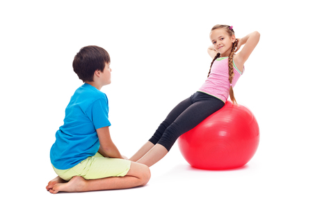 Kids exercising together using a large gymnastic rubber ball - helping each other, isolated