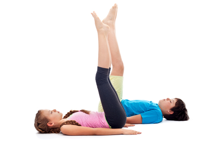 Kids doing gymnastic exercises on the floor - strengthening the legs and abdomens, isolated, copy space