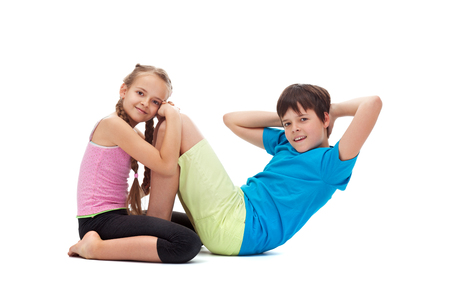 Kids doing gymnastic exercises together - helping each other strengthening their abdomens with sit ups, isolated