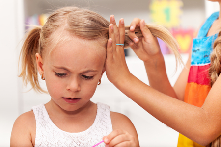 Older sister helps little girl tie her hair in plaits while playing, shallow depth Zdjęcie Seryjne