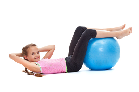 Young girl smiling and doing sit ups with a large gymnastic ball - strength and vitality concept, isolated Zdjęcie Seryjne