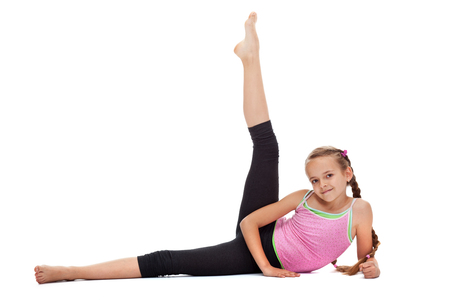 Young girl doing gymnastic exercises for leg strength and flexibility - lying on the floor, isolated Zdjęcie Seryjne
