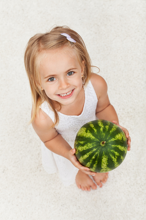 Happy healthy little girl holding a watermelon - looking up with a broad smile