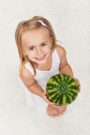 Szczęśliwa zdrowa mała dziewczynka trzyma arbuza - przyglądającego z szerokim uśmiechem up