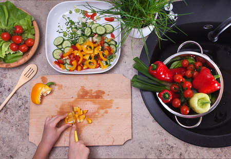 Hands chopping yellow bell pepper for a vegetable salad - healthy eating concept, top view of the cutting board and kitchen sink area Zdjęcie Seryjne