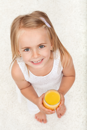 Little happy girl having a glass of fruit juice with a large smile on her face - top view Zdjęcie Seryjne