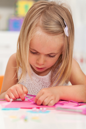 Little girl working on a crafting project - completely absorbed by the activity, closeup, shallow depth