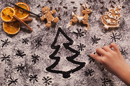 Child hand drawing holidays scene with xmas tree and stars in the flour prepared for the christmas cookies, shallow dept Zdjęcie Seryjne