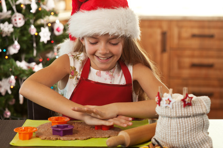 Girl in holidays mood making gingerbread cookies - cutting dough into christmas themed shapes, shallow depth