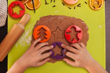 Child hands making gingerbread cookies - cutting christmas themed shapes from dough, top view