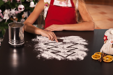 Young girl drawing christmas tree in the flour prepared to make cookies - closeup Zdjęcie Seryjne