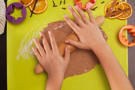 Stretching the christmas cookies dough - child hands with rolling pin, top view