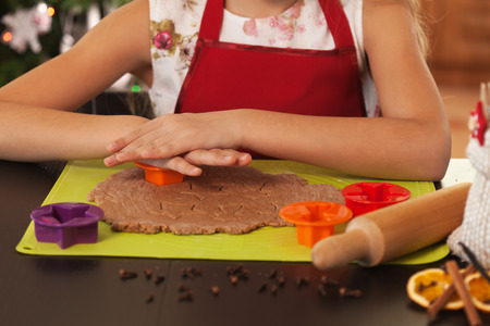 Child hands making christmas cookies - cutting the gingerbread dough, shallow depth