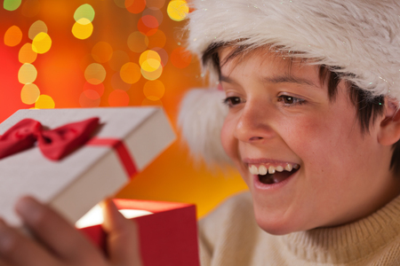 Young excited teenager boy opening his christmas present - closeup on happy face, shallow depth