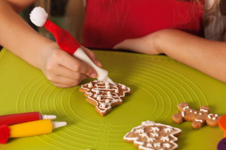 Child hands making christmas cookies, decorating a gingerb read xmas tree with white icing - closeup, shalllow depth Zdjęcie Seryjne