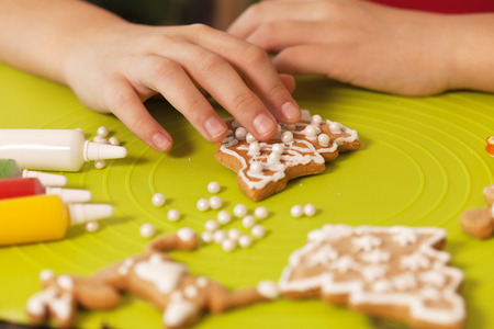 Child hands decorate christmas gingerbread cookies with sugar pearls - closeup, shallow depth