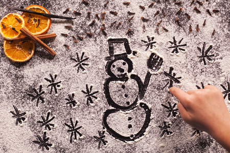 Waiting for the winter holidays - child hand drawing snowman and stars in the flour spread on black table