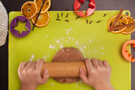 Kid hands stretching the gingerbread cookies dough - top viewshallow depth