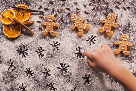 Child hand playing and drawing stars in the flour prepared for the christmas cookies, shallow depth Zdjęcie Seryjne