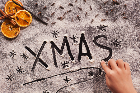 Child hand writing xmas in the flour prepared to make christmas cookies, shallow depth Zdjęcie Seryjne