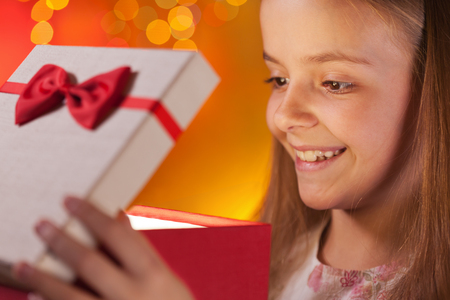 Young girl opening her christmas present - closeup on face, shallow depth