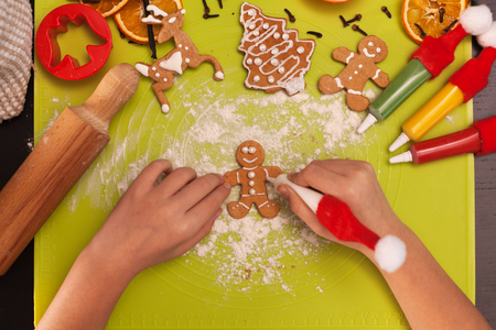 Child hands making gingerbread cookie people on the table - top view, closeup Zdjęcie Seryjne