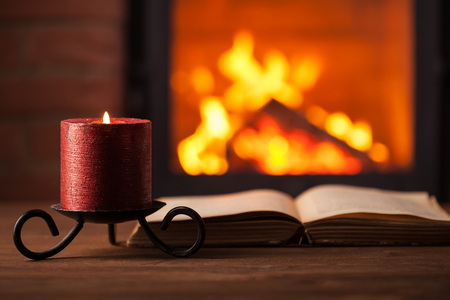 Reading by the fireplace - old book and candle against fire, on wooden surface