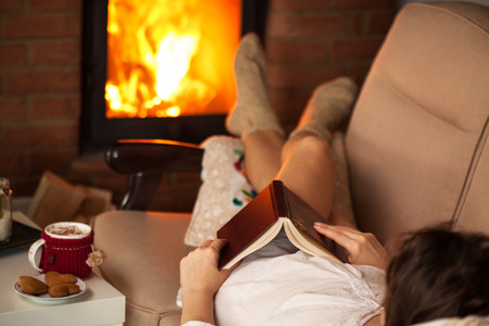 Woman relaxing by the fire with a good book some cookies and a cup of hot chocolate - watching the flames, shallow depth