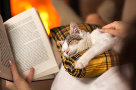Woman reading by the fire and comforting her rescue kitten - purrfect evening relaxation, closeup, shallow depth