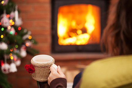 Woman enjoying a cup of latte coffee by the fireplace at christmas time - holidays season relaxing, shallow depth