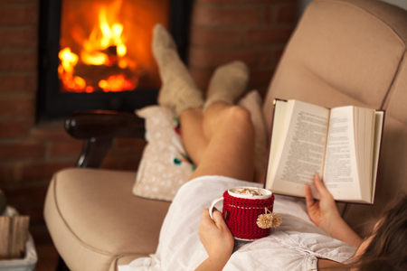 Woman enjoying a book and a hot chocolate drink by lying the fire on a sofa - focus on the cup and hand, shallow depth Zdjęcie Seryjne