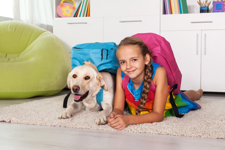 Young girl and her labrador dog ready for school - lying on the carpet at home