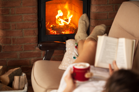 Woman enjoying free time by the fire - reading a book and sipping on a hot chocolate drink, focus on flames Zdjęcie Seryjne