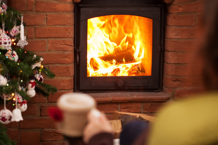 Woman watching the fire at the fireplace - sitting with a cup of coffee in christmas time - focus on the flames