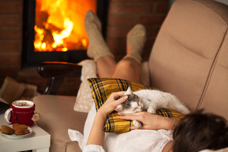 Woman enjoying the fire and some fine company - sharing the sofa with her kitten, shallow depth Zdjęcie Seryjne