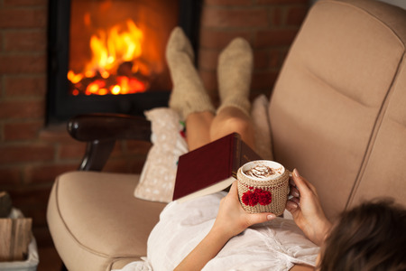 Woman relaxing by the fire holding a cup of hot chocolate with cream on top - lying on a sofa, shallow depth