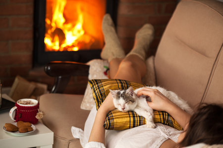 Woman caressing her new rescue kitten - lying on the sofa by the fireplace, relaxing together