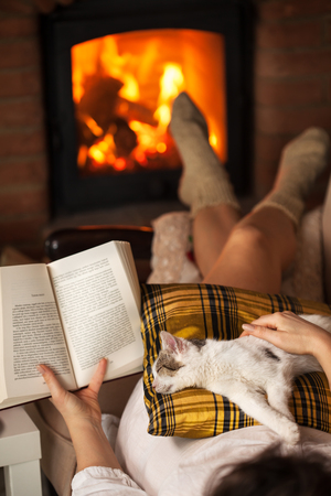 Woman reading by the fire - relaxing with her kitten lying on a sofa, shallow depth