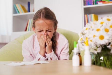 Young girl sneezing at home with paper towel prepared to blow her noise - allergy concept