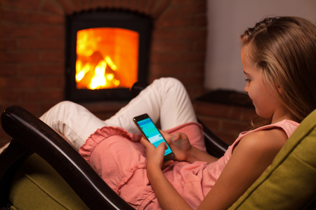 Young girl using smartphone sitting in front of fireplace in the evening - relaxation concept, shallow depth